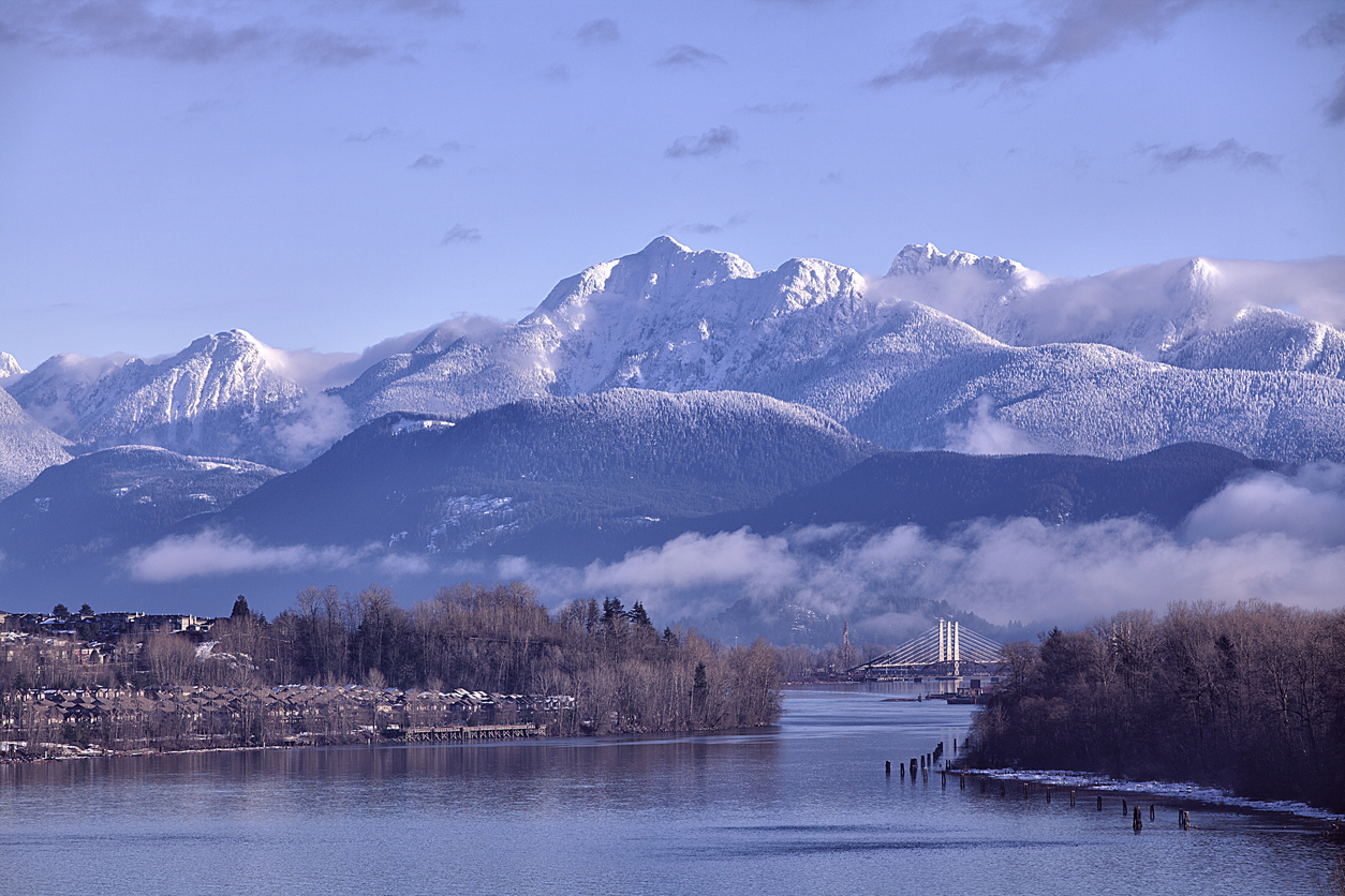 Fraser river in the morning seen from Surrey in winter, mountains heavily covered with snow.